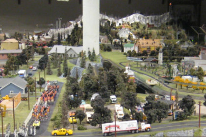 Shows a large model railroad, in the background you can see people walking around the perimiter