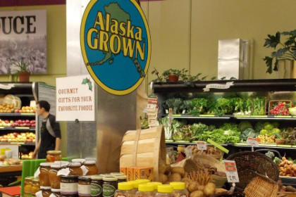 Display cases of vegetable produce with Alaskan grown sign above displays