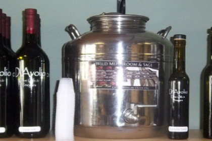 one of the large silver vats of flavored olive oil on hand for taste testing, surrounded by bottles of same oil