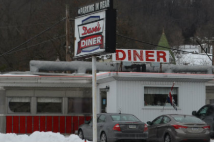 A white, 1950s looking diner with red trim and a red sign out front