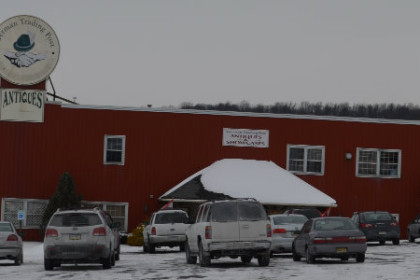 A large red warehouse wtih snow on the roof and cars parked out front. A round sign on the roof reads German Trading Post