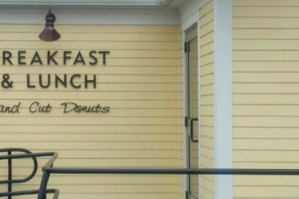 Yellow clapboard building with sign in black lettering reading Hole in One Breakfast and Lunch Hand Cut Donuts