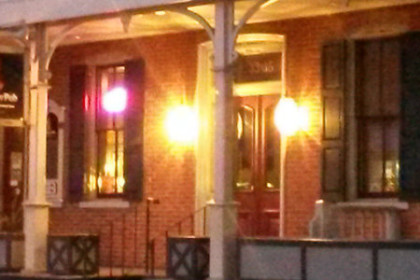 "shows the front porch of a brick building with the front lights on at night. There's a sign hanging from the porch that reads ""JoBoy's Brew Pub"""