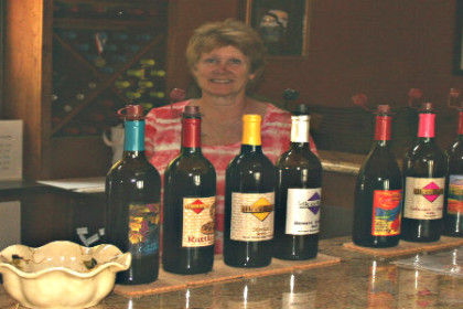 A lady standing behind a bar that has several wine bottles on it.