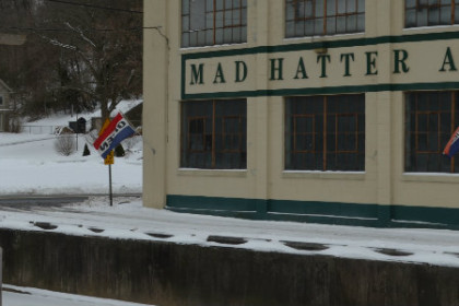 A large warehouse building with Mad Hatter Antiques painted on the outside