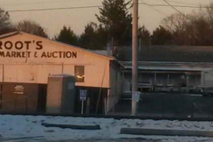 "A white, one-story building with ""Root's Country Market and Auction"" painted onto the side. The photo was taken in winter and there's snow on the ground."
