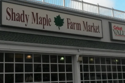 Shows the front of the Shady Maple Farm Market which is a row of multi-payned windows and a sign on top with the name of the market.