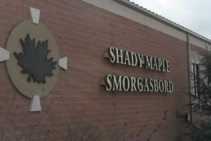 "Photo of a brick building with a sign that reads ""Shady Maple Smorgasbord"". There's a circle with a maple leaf on it to the left of the name."