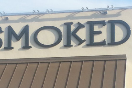 1 story building exterior of white stucco and large blue letters reading Smoked