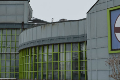 Grey building with lime green trim. Big glass window showing brewing equipment behind. Sign that reads Stoudts Brewing Company