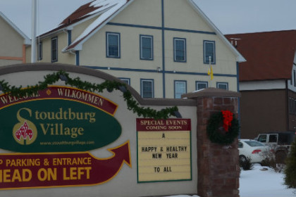 "Large sign that reads Stoudtburg Village with ""German"" looking buildings behind it."