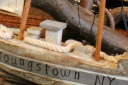 a hand carved wooden boat, with Youngstown written on the side, sitting on a shelf