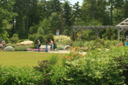 visitors in gardens with lawn, flowers, and trees