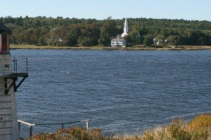 lighthouse looking over river to white church