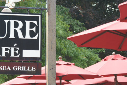 Black sign with white lettering over outside patio covered in red umbrellas
