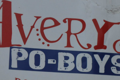 red, white and blue AQvery po-boy sign, oval shaped hanging over front entrance