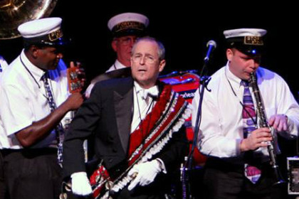 Brass band. Most men with white uniforms; grandmaster with black jacket and red, white and blue sash. All carrying brass musical instruments.