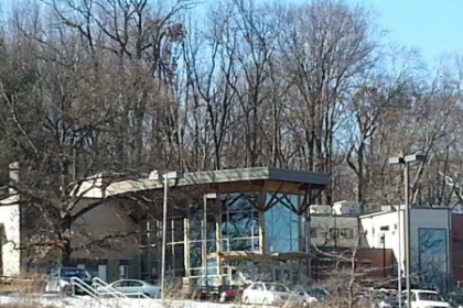 photo of the outside of the Wilderness Center, large brick and wood building surrounded by forest. Winter picture no foliage on trees, bright blue sky