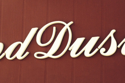 "The large, rust and cream exterior sign reads ""Bend Dusty's"""