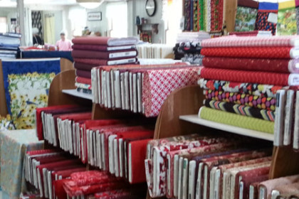 Beautiful display of multi colored bolts of fabric from one of the Quilting and Cuisine mini shop hop