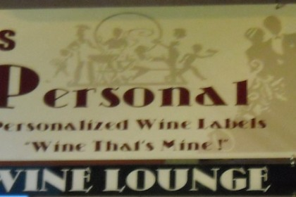 "Store sign with background pictures of a wine bottle and dancers that says ""It's Personal, personalized wine labels - Wine that's mine! - Wine Lounge"""