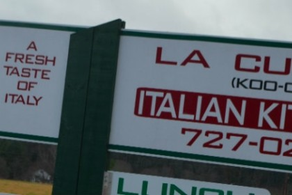 White sign with red letters saying La Cucina