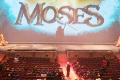 "Stage with the image of Moses parting the red sea projected to a screen on a large stage. ""Moses"" is writen in large font."