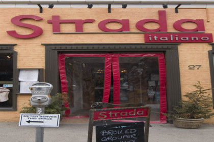 Peach colored walls with red lettering of the Strado Italiano restaurant