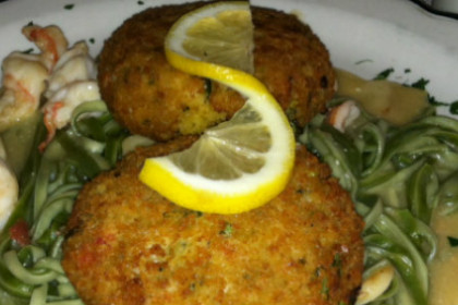 Two crab cakes and shrimp on a bed of spinach linguini.