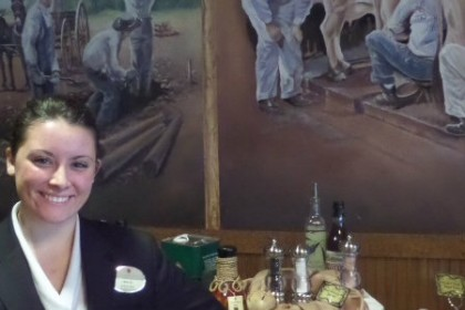 Keeter Center of College of Ozarks restaurant staff smiling in front of food station with murals of students milking cows and other scenes