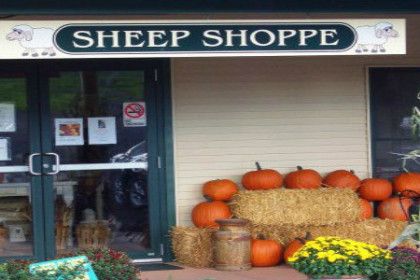 "facade of building with sign that says ""Sheep Shoppe"". Decorated with hay bales and pumpkins"
