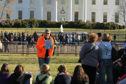 Group of people standing and listening to tour guide in front of White House