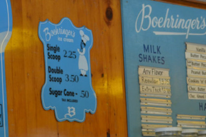 A wall with light blue signs hanging on it - one lists the ice cream selections for sale, the other is the traditional food menu