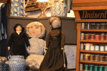 A display in an antique store with a shelf full of different color thread, three doll, some pottery and quilts... all nicely arranged