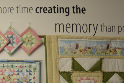 "Shows one of the shop walls where there's a graphic that reads ""Spend more time creating the memory than preserving it"". A collection of quilted crafts are hung round the quote."