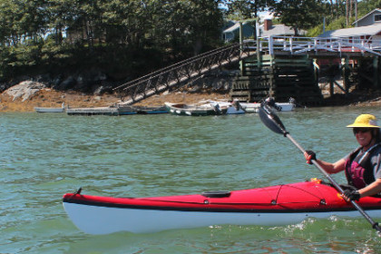 woman in red kayak paddling away from forested shore