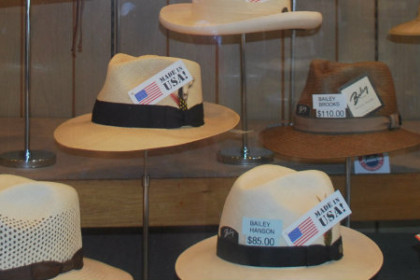 Glassed in showcase of an assortment of men's hats