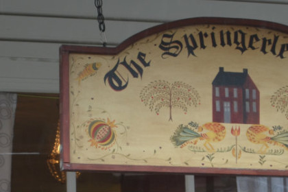 "A hand painted sign that reads ""The Springerle House"". There are other colonial-style images decorating the sign, making it look old"