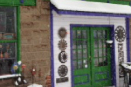 Front of old brick building with bright green and purple trim and hanging artwork on building and on blocks.