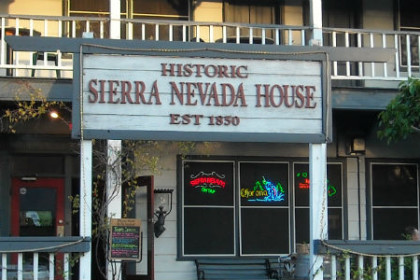 Exterior of Historic Sierra Nevada House Est. 1850 with people eating on decks