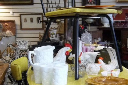 a yellow dinet with milk glass crockery and rooster decorations in front of a buffet on a wall of pictures and lamps