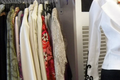 white jacket with black appliques to the right of a rack of blouses