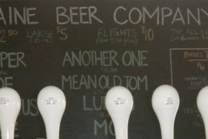 row of white handles for different beers on tap