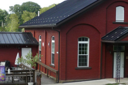 picture of School House Winery. Old school house building brick red with a black roof, deck with seating to the side of building