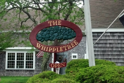"Gray shingled barn in the background with oval sign out front in cranberry and green reading ""The Whippletree"""