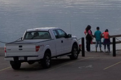 white pick up truck in front of Niagara River with people fishing on either side