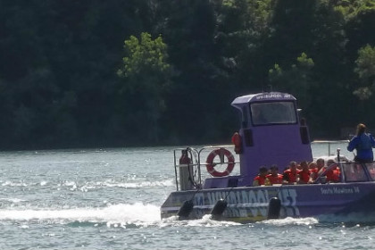 purple jet boat filled with orange life vest clad customers coming up the Niagara River and into Lewiston Harbor