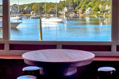 Round wooden tables overlooking the waterway