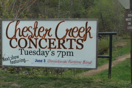 White sign with red letters reading, Chester Creek Concerts, Tuesday's 7pm, summer 2014
