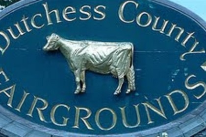 Rock wall with oblong sign attached that reads Dutchess county Fairgrounds and has a silver cow in center